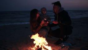 De moeder, vader in warme kleren roostert heemst op houten stokken met hun kleine baby Vuur op het strand stock footage