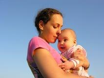 De moeder van gezichten met baby op de neus van de zonsondergangaanraking stock afbeelding