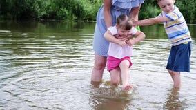 De moeder van het meisje wast zijn voeten in de rivier Een vrouw bevindt zich in het water met haar kinderen stock footage
