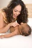 De moeder van Latina het spelen met haar zoon van de babyjongen op bed Royalty-vrije Stock Fotografie