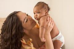 De moeder van Latina het spelen met haar zoon van de babyjongen op bed Stock Fotografie