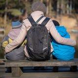 De moeder van twee jonge zonen zit op een parkbank royalty-vrije stock afbeelding