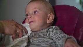 De moeder veegt het kindgezicht met keukenrol af stock video
