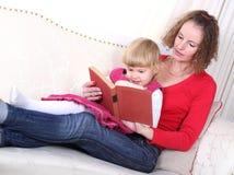 De moeder vertelt verhaal van boek in bed aan haar kind royalty-vrije stock afbeeldingen