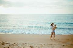 De moeder vervoert baby op het strand Royalty-vrije Stock Foto's