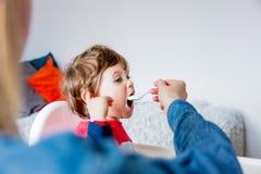 De moeder voedt een kleine peuterjongen met een lepel tijdens lunch stock foto's