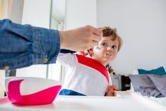 De moeder voedt een kleine peuterjongen met een lepel tijdens lunch stock afbeelding