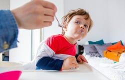De moeder voedt een kleine peuterjongen met een lepel tijdens lunch royalty-vrije stock foto