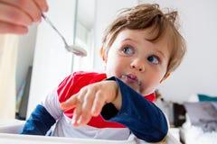 De moeder voedt een kleine peuterjongen met een lepel tijdens lunch royalty-vrije stock foto's