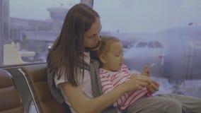 De moeder voedt haar weinig dochter met mandarijn bij luchthaven in langzame motie stock videobeelden