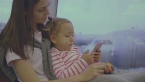 De moeder voedt haar weinig dochter met mandarijn bij luchthaven in langzame motie stock footage