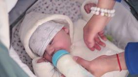 De moeder voedt de melk van het de peuterkind van de babyjongen van een plastic fles met een helder blauw uitsteeksel - Kaukasisc stock video