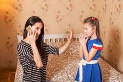 De moeder vraagt de dochter om stil te houden stock afbeeldingen