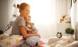 De moeder wekt haar dochter in bed in ochtend royalty-vrije stock afbeelding