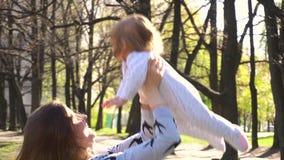 De moeder werpt haar babymeisje in de lente stock videobeelden