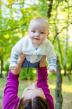 De moeder werpt omhoog gelukkige baby stock fotografie