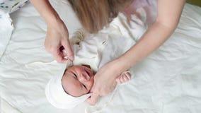 De moeder wikkelt haar kind in - pasgeboren babyzuigeling royalty-vrije stock afbeelding
