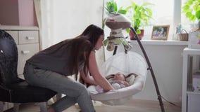 De moeder zet slaapbaby in de voederbak stock video