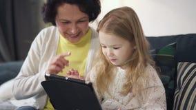 De moeder zit op bank, spreekt en toont aan dochter het beste gebruiken van laptop stock footage