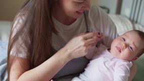 De moederglimlachen en raakt zacht haar pasgeboren baby stock video