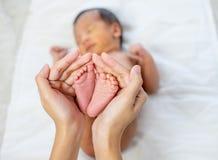 De moederhanden houden weinig pasgeboren babyvoeten met liefdeemotie en de baby slaapt op wit bed royalty-vrije stock foto's