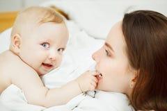 De moederspelen met blonde haarbaby, zuigeling heeft mollige wangen stock afbeelding