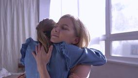 De moedertederheid, weinig dochter stort zich in moederwapens overhaast en geeft thuis grote omhelzing tegen venster in zonstrale