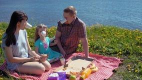 De de moedervader en dochter eten pizza door kustoverzees stock video