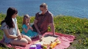 De de moedervader en dochter eten pizza door kustoverzees stock videobeelden