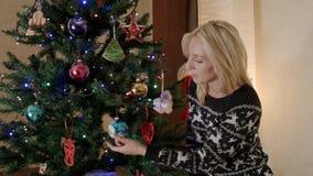 De moederzitting onder de Kerstboom met speelgoed en bewondert stock videobeelden