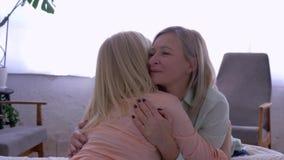 De moederzorg, glimlachende moeder met volwassen dochter omhelst terwijl thuis het babbelen