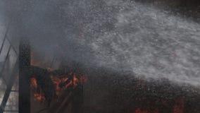 De moedige brandbestrijder dooft een sterke brand stock video