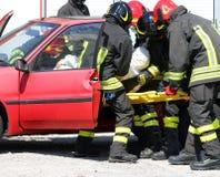 De moedige brandbestrijders in actie en trekken verwond Stock Fotografie