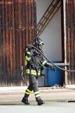 De moedige brandbestrijders met zuurstoftank steken tijdens een gehouden oefening in brand Royalty-vrije Stock Afbeeldingen