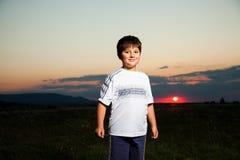 De moedige jongen glimlacht tegen de schemer met zon Stock Afbeelding