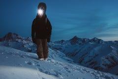 De moedige nachtontdekkingsreiziger beklimt op hoge berg Het dragen van koplamp, rugzak en skislijtage Snowboarder met een snowbo stock afbeeldingen