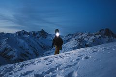 De moedige ontdekkingsreiziger met koplamp begaat een nacht beklimt aan een steile sneeuwberg Het dragen van skislijtage en rugza stock afbeelding