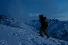 De moedige reiziger steekt de manier met een koplamp bij de berg van de nachtwinter aan Snowboarder met rugzak en een snowboard a royalty-vrije stock foto's
