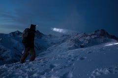 De moedige reizigersmens begaat skireis op hoge berg bij nacht Professionele snowboarder steekt de manier met een koplamp aan Bac stock afbeeldingen