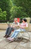 De mogna paren vilar på stor balkong i sommartid Royaltyfri Bild