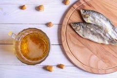 De mok en de snacks van het lagerbierbier op witte houten lijst stock foto's