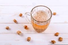 De mok en de snacks van het lagerbierbier op witte houten lijst stock foto