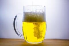 de mok met licht bier giet Stock Fotografie