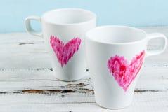 De mokken van de paarkoffie met harten met lippenstift worden geschilderd die Stock Afbeeldingen