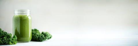 De mokken van de glaskruik met groene gezondheid smoothie en boerenkoolbladeren De ruimte van het exemplaar Ruw, alkalische vegan Royalty-vrije Stock Foto