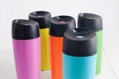 De mokken van kleurenthermosflessen op de witte houten lijst Stock Foto's