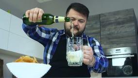 De mollige kerel met baard in schort giet bier in een mok aan chips De chips zijn in een plaat Alcoholische drank en stock footage