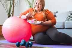 De mollige vrouwensport die thuis het leunen op de cake van de balholding zitten behandelt na opleiding vrolijk glimlachen stock foto