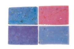 De Molticolorzepen met de hand gemaakt met organische olie van lavendel ond een andere bloeit geïsoleerd op wit royalty-vrije stock afbeeldingen
