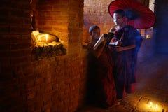 De monnik bidt met kaars in Bagan, Myanmar Stock Foto's